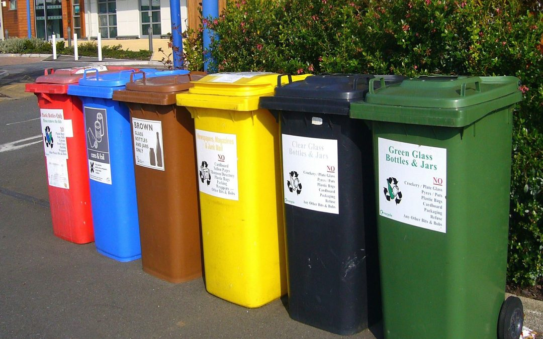 Colorful recycling bins lined up on the street.